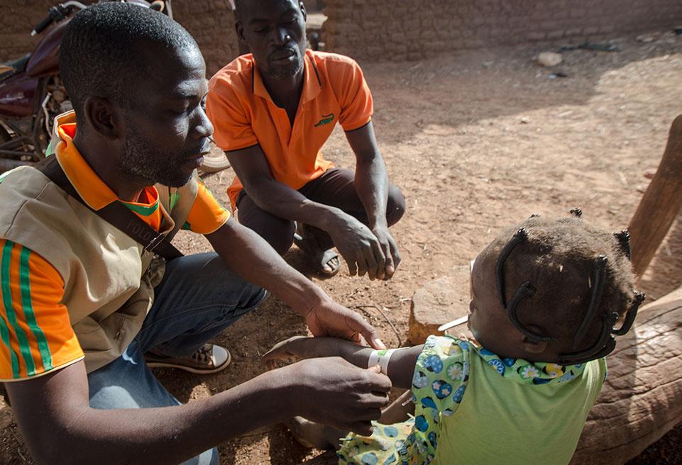 Teabda Abdoul Aziz dépiste la malnutrition chez Ouedraogo Louisa, 4 ans, à l'aide du MUAC, dans le cadre d'une enquête mobile de dépistage de la malnutrition à Yako. Son père, Lamine, la regarde.