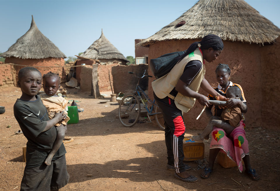Ilboudott Isabelle dépiste Valeá Evardé dans le cadre d'une enquête mobile de dépistage de la malnutrition à Yako.Sa mère, Florence, la regarde.