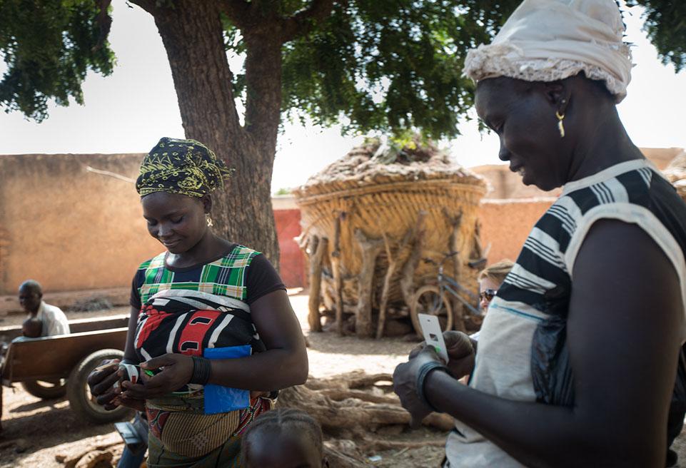 Les mères dépistent la malnutrition chez leurs enfants grâce au bracelet MUAC dans le village de Tindila.