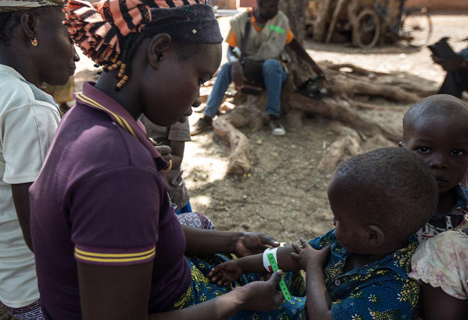 Fatima Sankara dépiste son fils VALEA Taoufik, 3 ans, à l'aide d'un ruban MUAC dans le village de Tindila lors d'une visite de l'équipe mobile d'ALIMA.