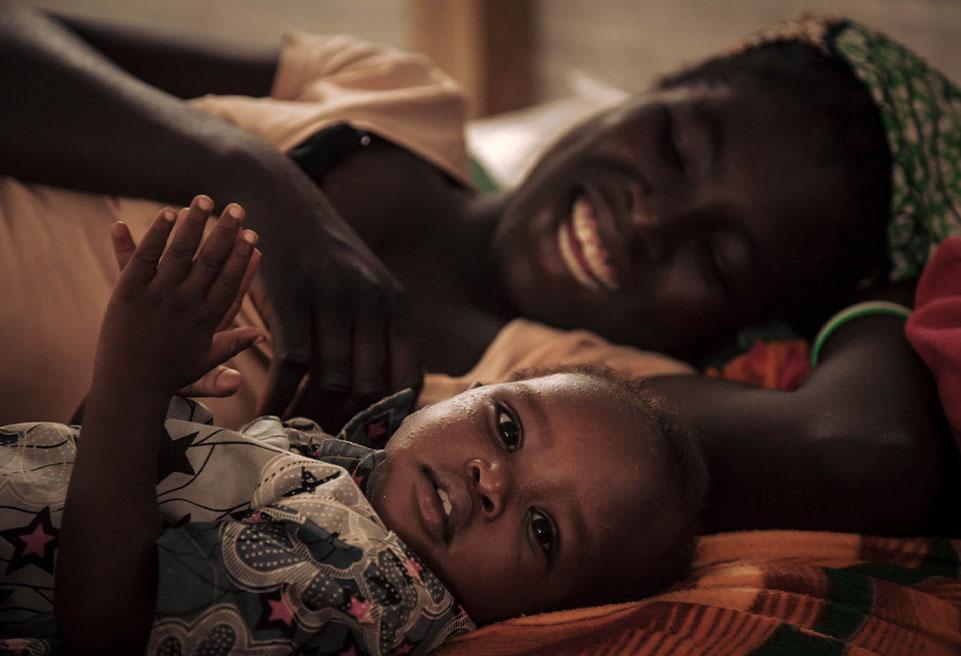 Delphine NGUIZIYÉ, 22 ans, et son fils de 15 mois Boné ZRA, jouent dans la salle de la phase de transition du CNTI de Mokolo. Boné a été admis au CNTI car il refusait de s'alimenter.