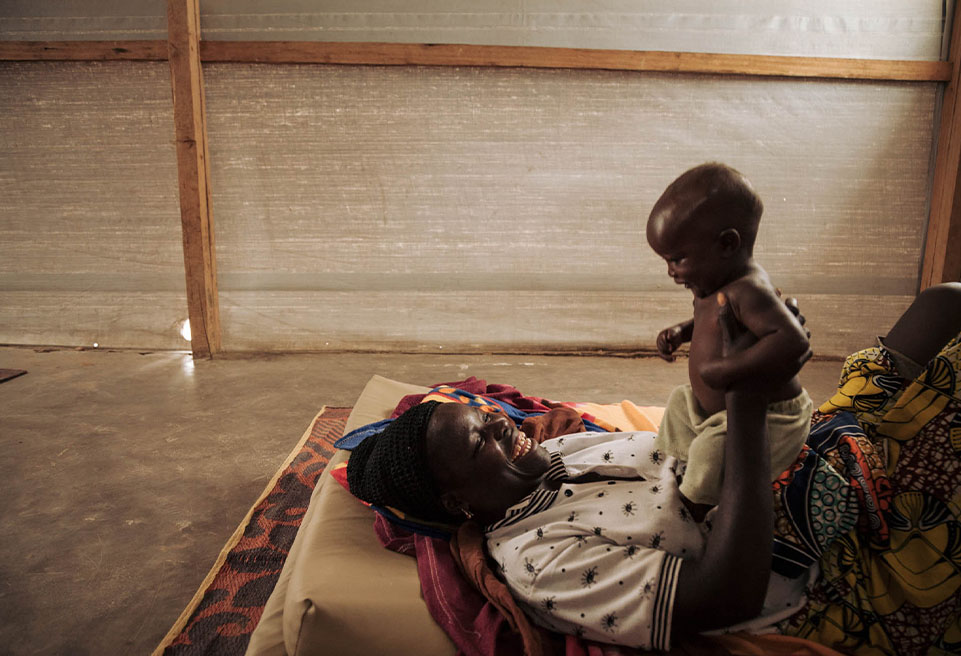 """Margareth BITROS, réfugiée nigériane, joue avec son fils de 8 mois, Yacoubou, dans la salle de la """"phase de transition"""" du CNTI de Mokolo."""