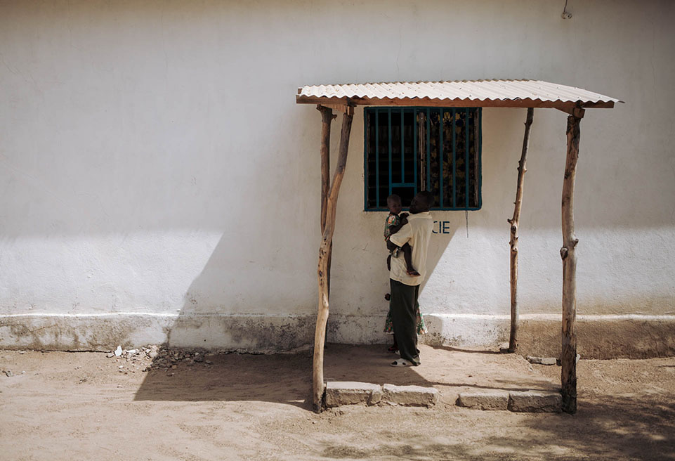 Un homme et ses deux filles attendent devant la pharmacie d'un centre de santé urbain à Koza.