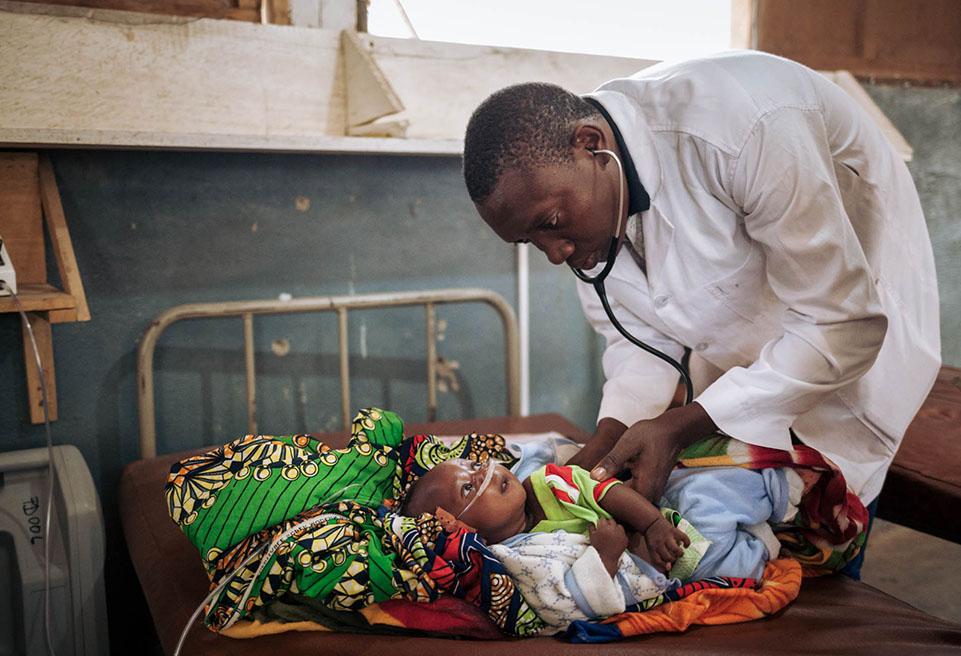 Christian, médecin chez ALIMA, examine Ali Ali (3 mois), admis en soins intensifs en état de détresse respiratoire à l'hôpital de Mokolo. Il est enfant de Kaltoum IBRAHIM, réfugiée au camp de Minawao.