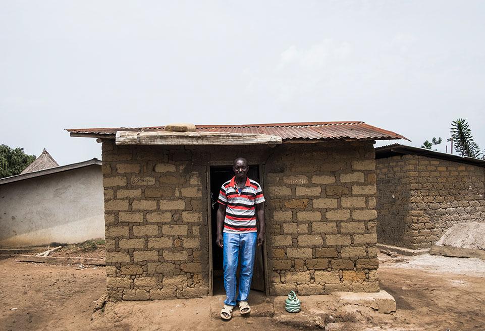 Amadou Camara, survivant du virus Ebola, devant sa maison à Koropara. Amadou bénéficie d'un traitement médical fourni par ALIMA.