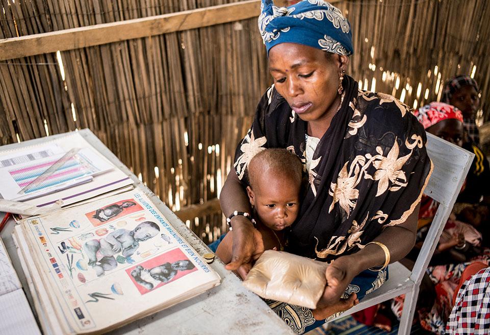 Un promoteur de la santé donne une formation à Rabi Seydou, 30 ans, accompagnant son enfant de 18 mois. On lui enseigne à mesurer elle même son périmètre brachial et contrôler si il a des œdèmes