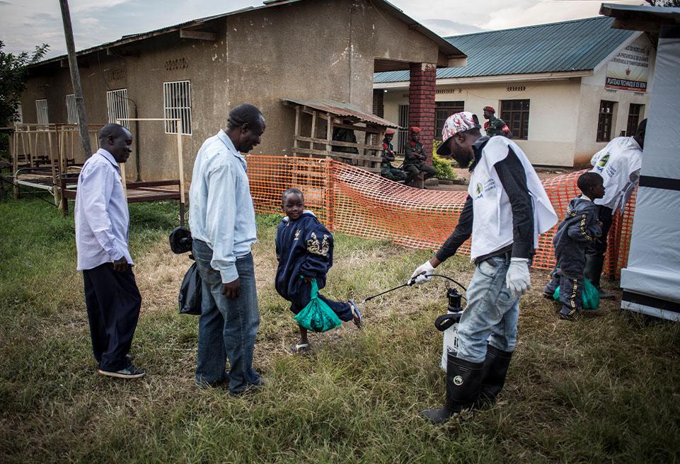 Un père regarde son fils se faire nettoyer les pieds à la sortie du centre de traitement d'Ebola après que la suspicion de contamination ait été écartée