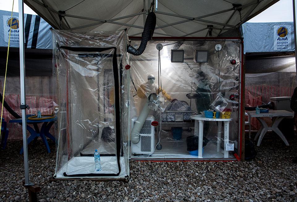 Trois travailleurs médicaux d'ALIMA examinent un patient atteint d'Ebola dans une CUBE à Beni