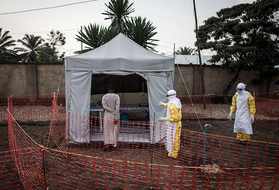 Un patient atteint d'Ebola non confirmé est conduit par deux travailleurs médicaux dans son nouveau service du nouveau centre de traitement Ebola