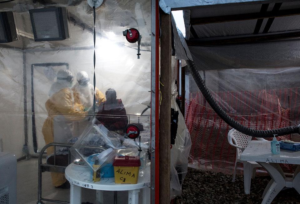 Deux travailleurs médicaux d'ALIMA surveillent un patient atteint d'Ebola dans une CUBE