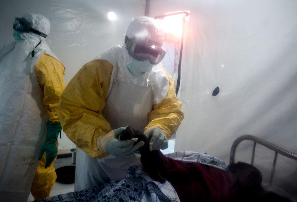 Un patient atteint d'Ebola est examiné par deux travailleurs médicaux après avoir été conduit dans une CUBE