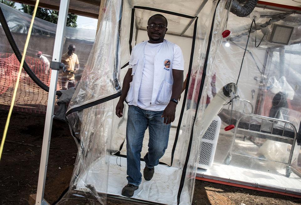Jackson Katembo, membre du personnel d'ALIMA,sort des Unités de soins d'urgence biosécurisées (CUBE)