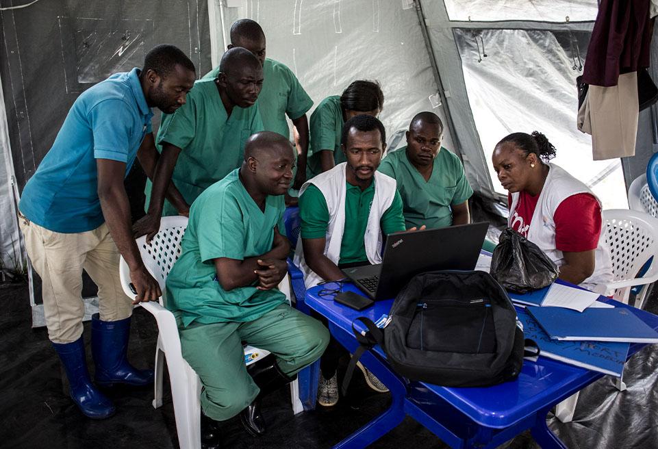 Le docteur Sylla Aboubabcar, membre du personnel d'ALIMA, explique le protocole d'hygiène correct pour le virus Ebola au personnel d'entrée du traitement