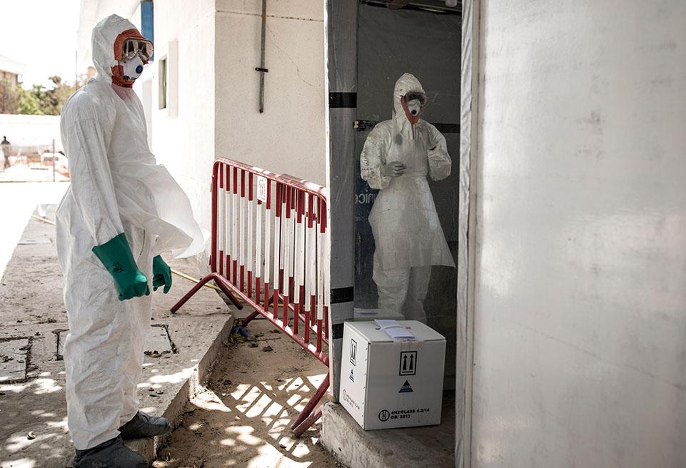 Un hygiéniste attend pour enlever et désinfecter son équipement de protection après avoir désinfecté la zone abritant les patients infectés par la COVID-19