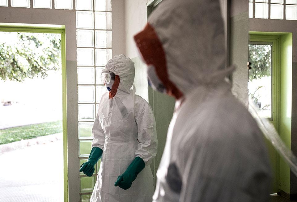 Des hygiénistes avec leur équipement de protection avant le nettoyage du service accueillant les patients infectés