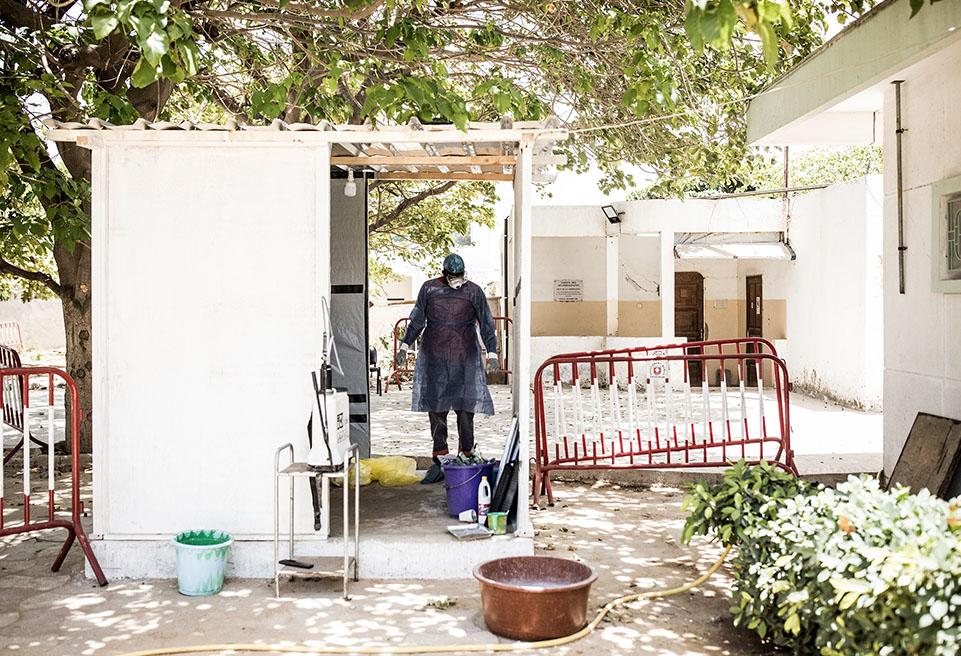 Un hygiéniste travaillant avec le ministère sénégalais de la santé attend pour enlever et désinfecter son équipement de protection