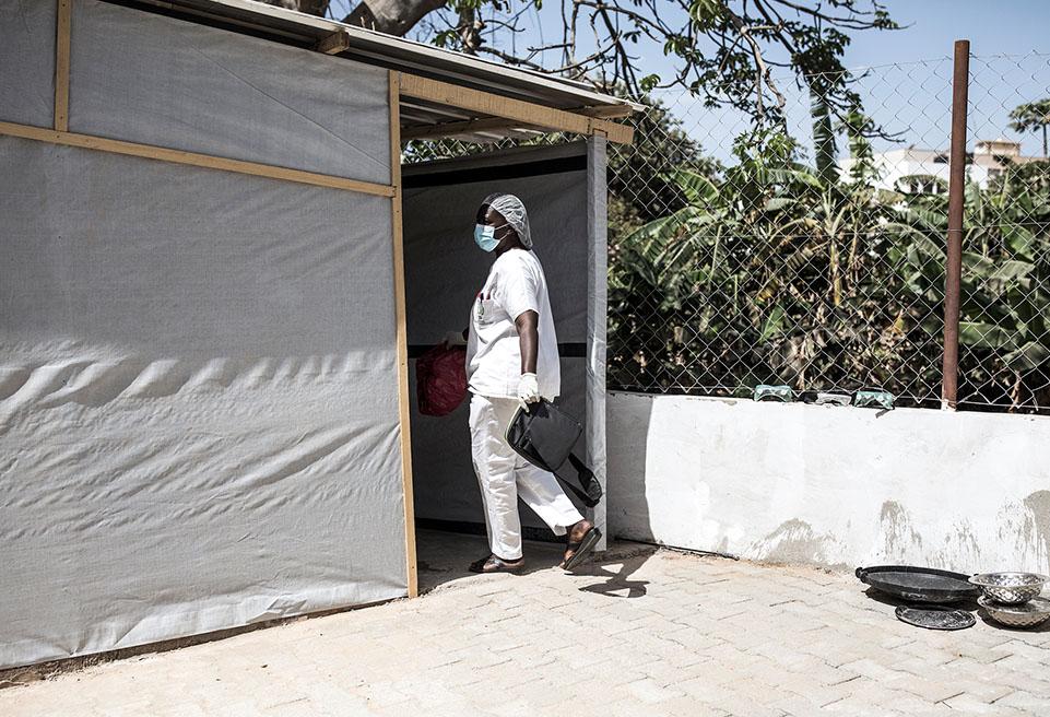 Une hygiéniste travaillant pour le ministère sénégalais de la santé transporte des sacs infectés récupérés dans la chambre d'un patient malade