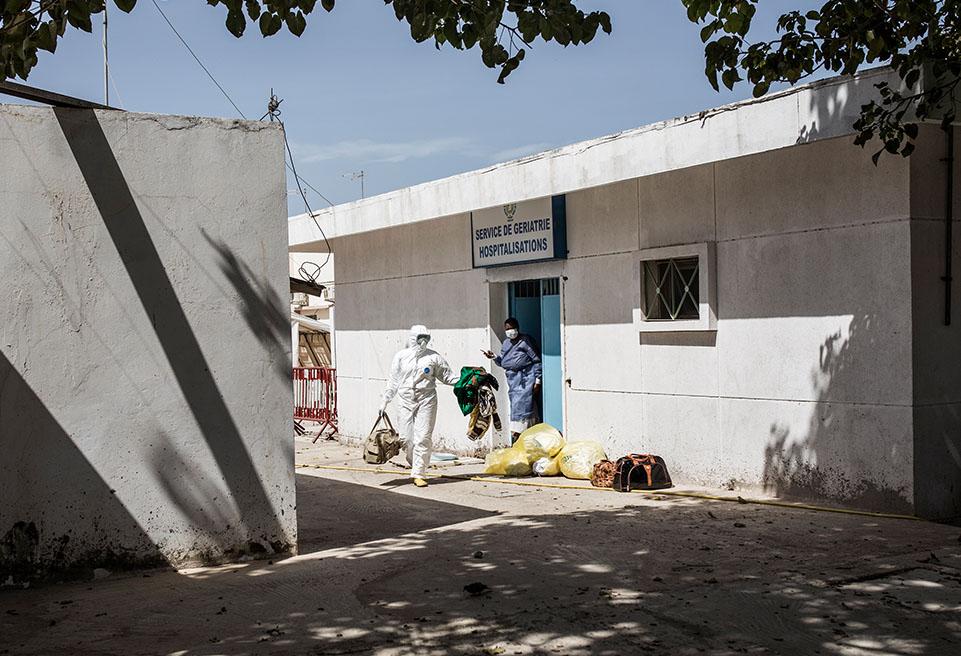 Des hygiénistes travaillant pour le ministère sénégalais de la santé devant le service s'occupant des patients confirmés atteints du virus à l'hôpital Fann de Dakar
