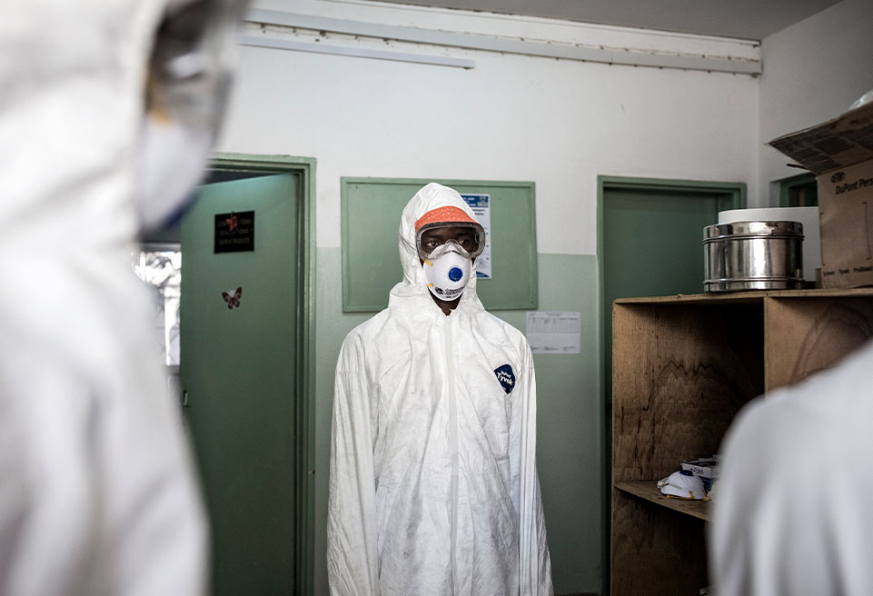 Un hygiéniste en équipement de protection, désinfecte la zone accueillant les patients.  ALIMA soutient le ministère de la Santé, en renforçant leurs capacités de prévention et contrôle des infections